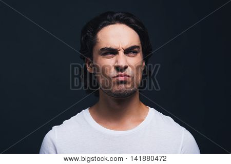 Making a face. Portrait of young man expressing disgust and looking away while standing against grey background