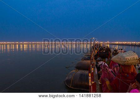 ALLAHABAD INDIA - FEB 12 - Hindu pilgrims cross a pontoon bridge into the massive campsite during the festival of Kumbha Mela on February 12th 2013 at Allahabad India.
