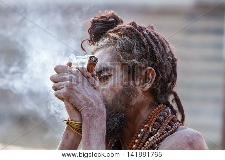 A Hindu Sadhu Smoking A Hash Pipe - India.
