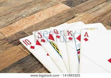Poker cards, Royal flash on wooden background. Macro shot.