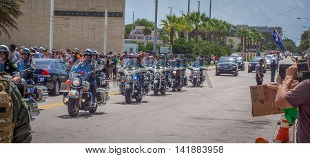 Daytona Beach, FL - August 3, 2016: A police escort leads the way as Donald Trump holds a rally in Daytona Beach, FL.  Protestors attend the rally on the right side and supporters stand in line to get in the arena on the left.