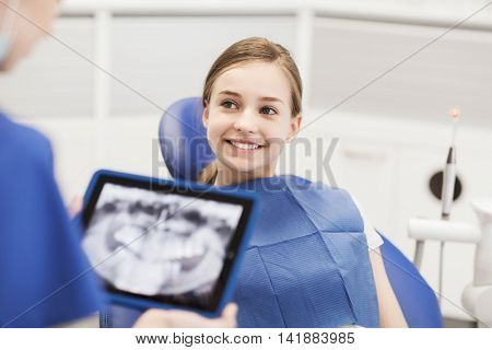 people, medicine, stomatology, technology and health care concept - dentist with x-ray on tablet pc computer and girl patient