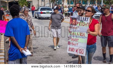 Daytona Beach, FL - August 3, 2016: Protestors and Supporters clash in Daytona Beach at a Donald Trump rally.  Police stand by in the background to keep the peace.