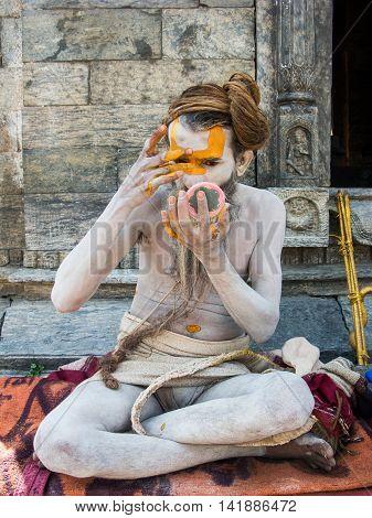 NEPAL, KATHMANDU, May 6th 2014 - A Hindu holy man adorns himself with sacred clay at the shrine of Pashupatinath.