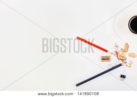 Top view of white desktop with pencils sharpener sawdust small peg and coffee cup