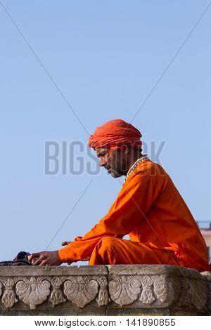 VARANASI, INDIA - FEB 18 - A Hindu holy man studying a Sanskrit text.