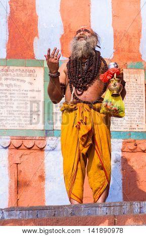 VARANASI, INDIA - FEB 18 - A Hindu yogi at the ghats of Varanasi offering morning prayers to the sun on February 18th 2013