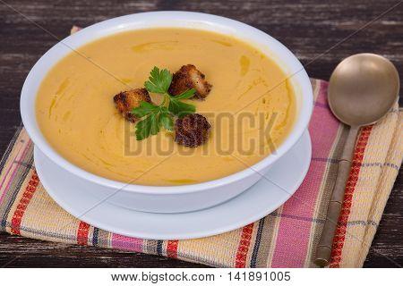 Apple pumpkin cream soup in a dish. Close up