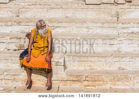 VARANASI, INDIA - FEB 18 - A sadhu sits on the ghats overlooking he Ganges river at Varanasi on February 18th 2013