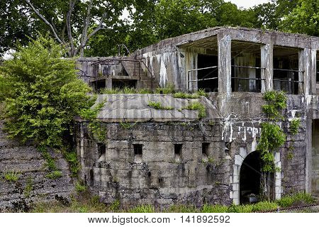 Battery Decatur and Disappearing guns ruins with overgrown foliage at Ft. Washington National Park a Military fort established in the 1800's to protect Washington DC situated on the Maryland coastline of the Potomac River