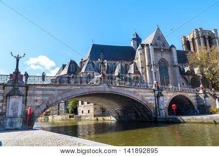 Ghent, Belgium - April 12, 2016: Medieval St. Michael Bridge, church, canal, people in Ghent, Belgium
