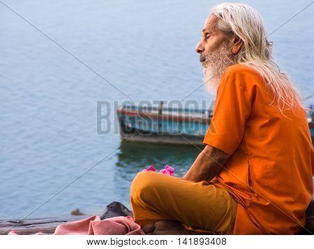 22nd May 2008, Varanasi, India - A sadhu sits overlooking the Ganges River.