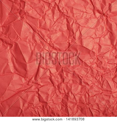Close-up fragment of a red crumpled paper texture as a backdrop composition