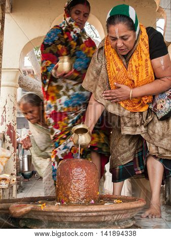 VRINDAVAN, INDIA - OCT 10th - A group of Hindu women worship a Shiva linga in a shrine in Vrindavana, India on October 10th, 2009