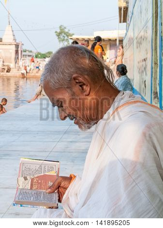 VRINDAVAN, INDIA - OCT 15 - An old sadhu reading a Hindu scripture on the banks of the sacred pond of Radha-Kunda in Vrindavan,on October 15th 2009