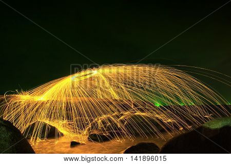 Hot Golden Sparks Flying from Man Spinning Burning Steel Wool into a Sphere on a Rocky Shoreline. Long Exposure Photography using Steel Wool Burning.