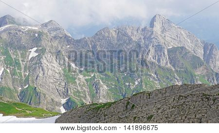 Hikers on the way to the peak of Santis, landscape in the high mountains of the Alpstock-massif in Switzerland