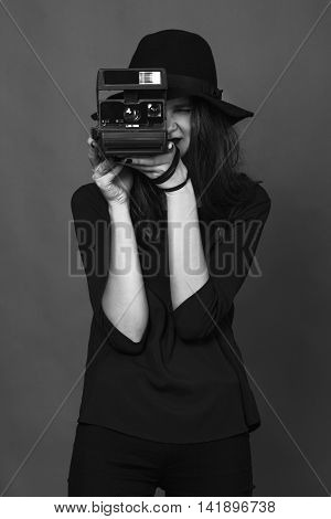 Girl with brown hair in a dark felt hat is photographed on Polaroid