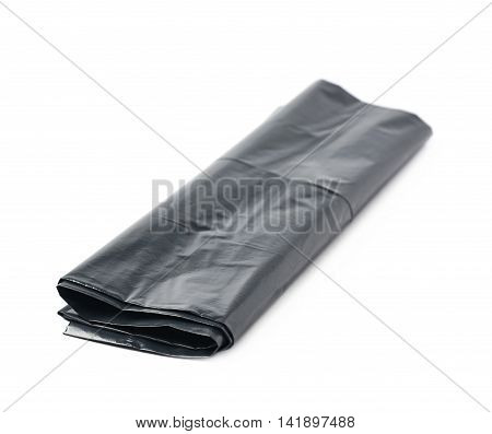 Single black plastic polyethylene trash bag folded and isolated over the white background