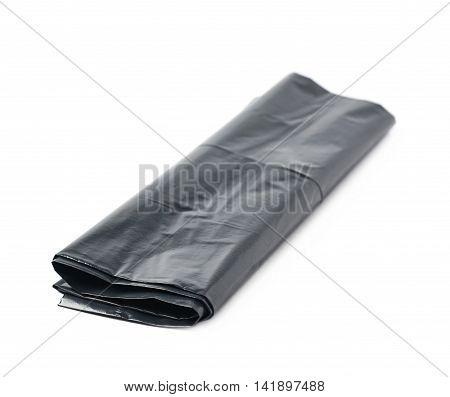 Single black plastic polyethylene trash bag folded and isolated over the white background