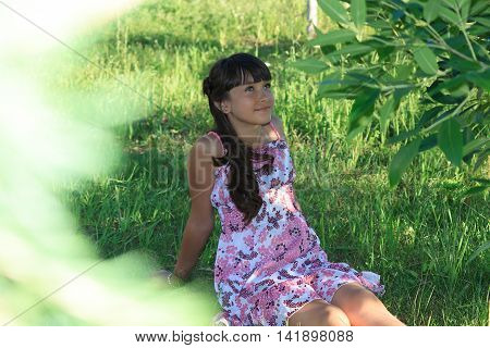 Beautiful teenage girl in pink dress with long hair in a green summer park horizontal view