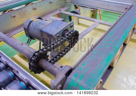 Motor chain drive shaft in conveyor line.