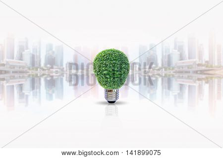 Energy saving lamp of tree with shadow on blurred skyscraper background. Concept for saving energy, global warming, Earth Day, Go Green and save the world.