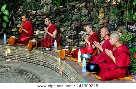 Chiang Mai Thaland - December 26 2012: Five monks in burgundy robes hands clasped in prayer before eating lunch seated on a curved stone bench at Wat Palad *