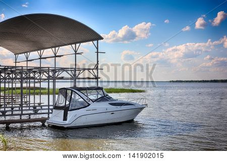 Boats parking - The modern powerboat on the mooring on cloudy the sky a background