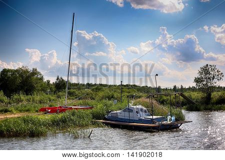 Boats parking - The old powerboat and sailing catamaran on the parking on cloudy the sky a background