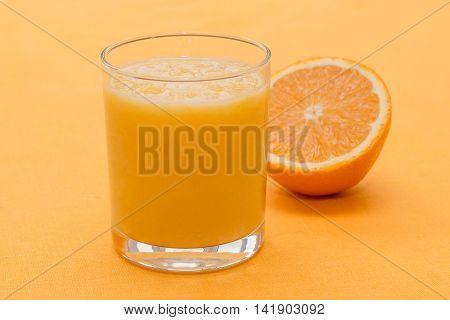 Orange Smoothie In Glass On Orange Background