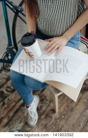 girl having a break with cup of coffee after reading books.