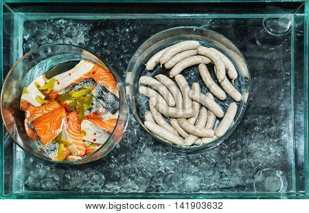 Salmon chunks and sausage in a glass bowl cooling on ice ready for grilling top view.