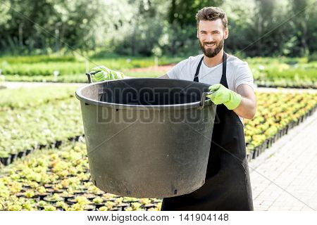 Handsome gardener holding huge bucket for growing trees on the plantation