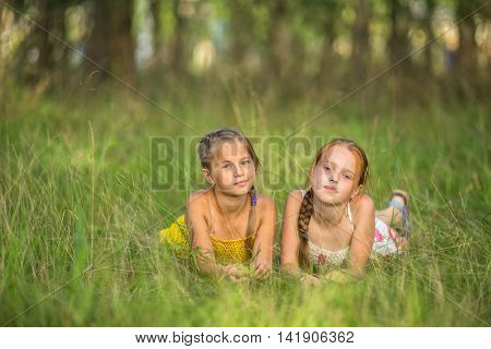 Two little sisters lying in the meadow looking at the camera.