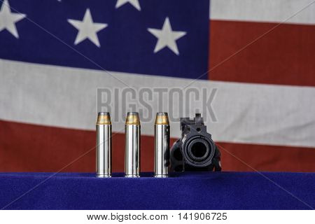 three bullets and 357 magnum revolver on blue with american flag background