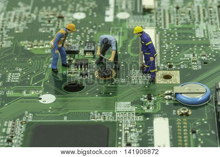 mini worker try to remove screw on mainboard with engineer control - can use to display or montage on products