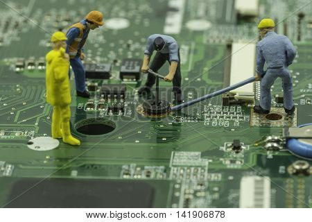 mini workers team try to remove screw from green mainboard - can use to display or montage on products