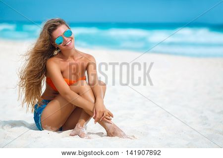 Happy young brunette woman with long blonde hair,a beautiful smile and white straight teeth, sitting on the white sand of a tropical beach near the blue ocean,dressed in blue shorts and an orange bra on a bathing suit,wears blue sun glasses