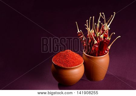 chilly powder with red chilly in clay pots, dried chillies on dark background