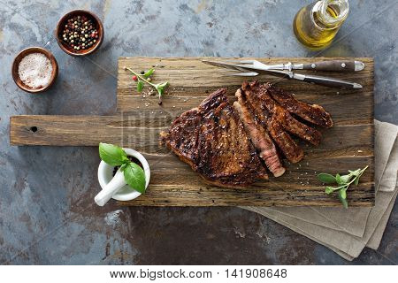 Ribeye steak seared to medium well on a cutting board top view with herbs, salt and pepper