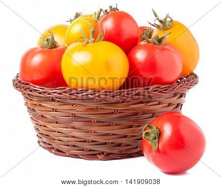 red and yellow tomatoes in a wicker basket isolated on white background.