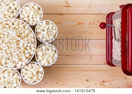 Bowls Of Fresh Popcorn Alongside A Machine