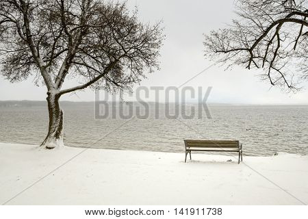 An image of a bench in a snowy winter scenery