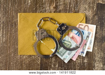 Envelope with Euro bills and handcuffs over wooden background