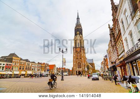 Delft, Netherlands - April 6, 2016: Colorful street view with Nieuwe Kerk or New Church, traditional dutch houses, people walking