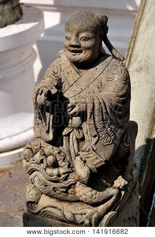 Bangkok Thailand - January 19 2013: Carved stone statue of a Chinese nobleman on a stair balustrade at Royal Wat Boworniwet