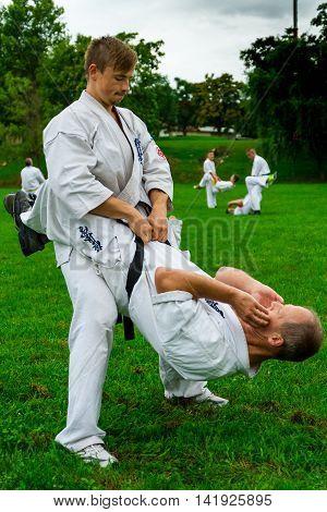 Miskolc Hungary - August 2. 2016: Athletes perform abdominal exercises holding partner of the belt during the international summer training camp for Kyokushin Karate.