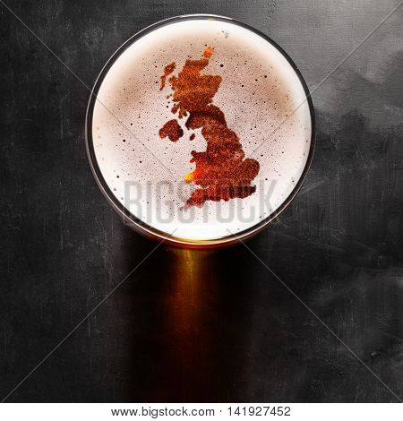 English beer concept, Great Britain silhouette on foam in beer glass on black table. Elements of this image furnished by NASA