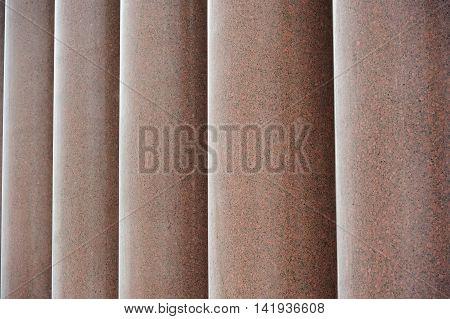 A row of massive red granite columns
